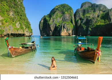 Young woman sitting on the beach at  Maya Bay on Phi Phi Leh Island, Krabi Province, Thailand. This island is part of Mu Ko Phi Phi National Park.