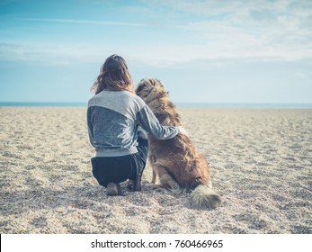 A young woman is sitting on the beach with her big Leonberger dog