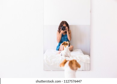 young woman sitting on bed and taking a picture with a reflex camera to her cute small dog on the mirror. Daytime. LIfestyle with pets