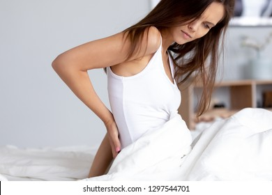 Young woman sitting on bed rubbing back feeling hurt ache morning discomfort lower lumbar muscular pain, upset female waking up with backache after night sleep on bad mattress, backpain concept