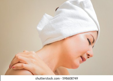 Young woman sitting on the bed suffering from pain in shoulder, isolate on warm tone