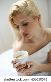 Young woman sitting on bed and holding cup of coffee.