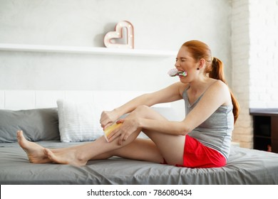 Young woman sitting on bed, doing routine leg waxing. The redhead girl bites a hairbrush to stand the pain while she pulls the strip, then faints back