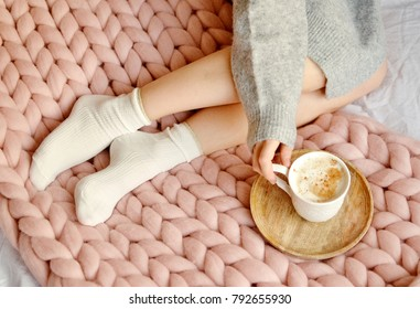 Young Woman Sitting on the Bed with Pink Giant Merino Wool Plaid Blanket with Cup of Cappuccino Toned Photo Morning Concept Vintage