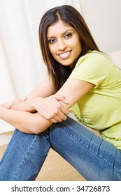 young woman sitting on bedroom floor