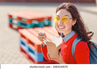 young woman, sitting on the bench at city street and holding a fast food lunch box, healthy and tasty meal while break in office