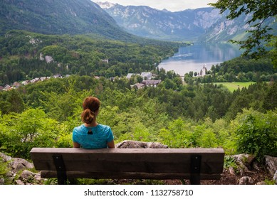 Young woman is sitting on a bench and admiring panoramic view of lake Bohinj in Bohinj, Slovenia