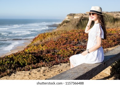 Young woman sitting on the bench at the atlantic coast looking at the sea. Portugal
