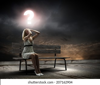 Young woman sitting on bench closing eyes with palms