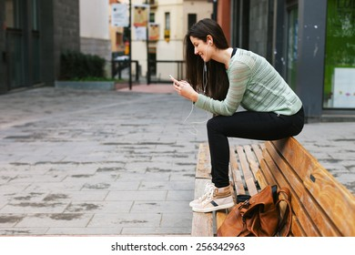 Young woman sitting on a bench in the city./ Young beautiful woman listening to music with phone in outdoors.