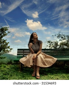 young woman sitting on a bench in a park
