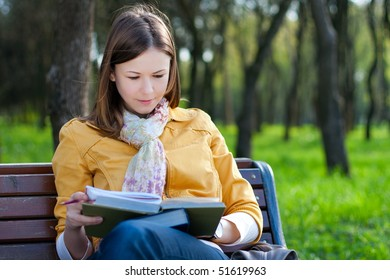 young woman sitting on the bench and reading book