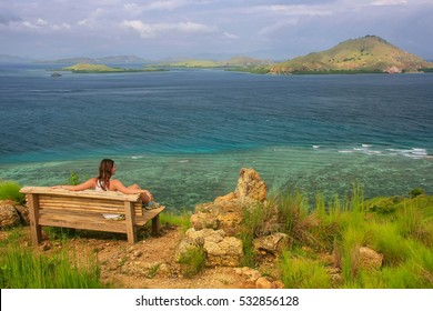 Young woman sitting on a bench at the viewpoint on Kanawa Island in Flores Sea, Nusa Tenggara, Indonesia. Kanawa Island is within the Komodo National Park.