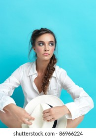 young woman sitting on blue background, with white hat and man's shirt, copy space