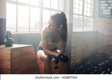 Young woman sitting on a box at gym after her workout. Female athlete taking rest after exercising at gym.