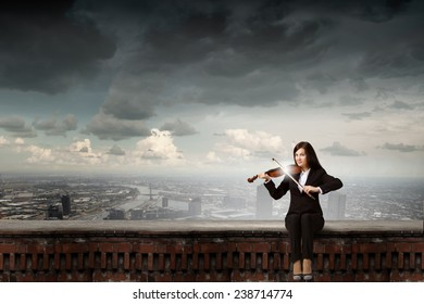 Young woman sitting on building top and playing violin
