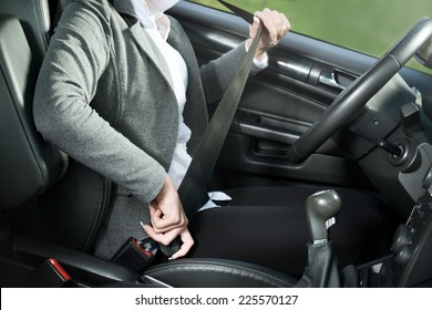 Young woman sitting on car seat fastening seat belt.