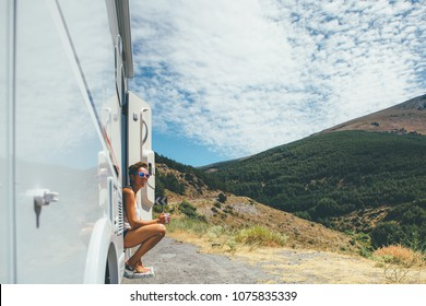 Young woman is sitting on a caravan step and holding a cup on a holiday adventure trip stop. Copy space area available