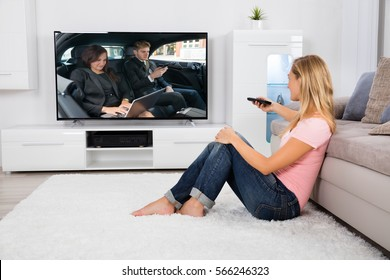 Young Woman Sitting On Carpet Watching Movie On Television At Home