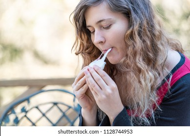 Young woman sitting on chair, holding, eating one piece of homemade mochi sticky glutinous Japanese rice cake dessert outdoors, outside on deck