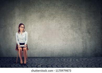 Young woman sitting on chair with paper waiting for job interview and looking nervous