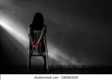 Young woman sitting on chair and  tied up with rope ,Victim woman tied with red rope sit on chair in abandon house,Sexual abuse or rape in dirty room with copy space,mono tone .