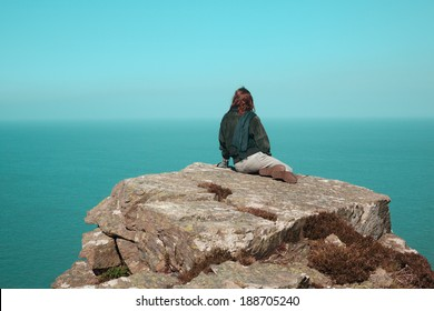 Young woman is sitting on a cliff by the sea