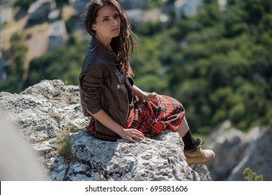 Young woman sitting on cliff and enjoy the view. A girl in a kilt, a Scandinavian mood. Crimea, Mount Cat