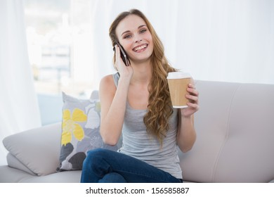 Young woman sitting on couch holding disposable cup on the phone at home in the living room
