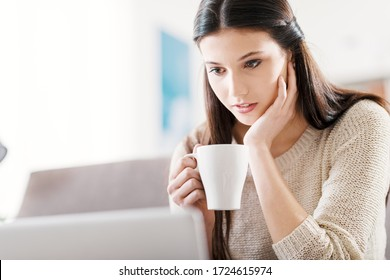 Young woman sitting on the couch at home and watching a movie streaming online on her laptop, she is holding a cup of coffee