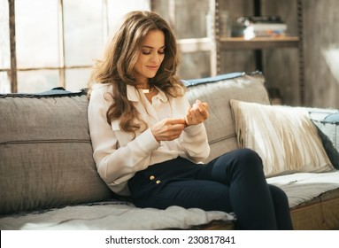 Young woman sitting on couch in loft apartment