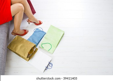 Young woman sitting on couch after day of shopping,  colorful shopping on the floor.