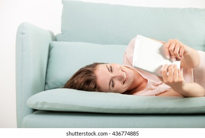 Young woman sitting on couch at home and reading ebook on tablet computer, casual style indoor shoot