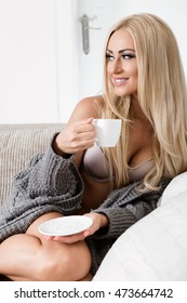 young woman sitting on couch with a mug. cozy mood