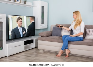 A Young Woman Sitting On Couch Watching Movie On TV In Living Room At Home