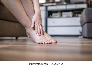 Young woman sitting on the couch suffering from severe pain in the leg. Woman having leg injury, healthy concept. Pregnant woman massaging her painful foot,