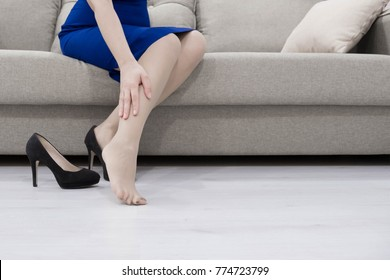 Young woman sitting on the couch suffering from severe pain in the leg
