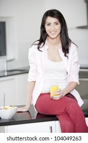 Young woman sitting on counter drinking orange juice