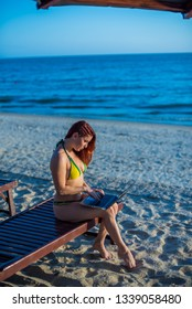 A young woman is sitting on a deck chair with a laptop next to the sea. Work in travel. Freelancer