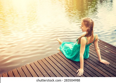 Young woman sitting on a deck by the water, looking into the distance. Carefree bright future concept. Beautiful woman on wooden pier by the lake outdoors. Lens flare sunlight, filter.