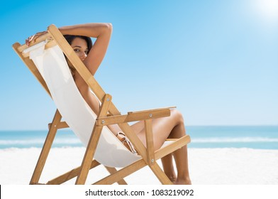 Young woman sitting on a deckchair and looking at camera. Relaxed beautiful girl enjoying the sea with copy space. Smiling woman lying on a deck chair while enjoying sunbathing at beach.