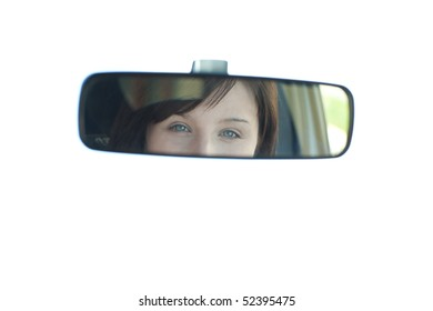 Young woman sitting on driver's seat and looking in the rear-view mirror