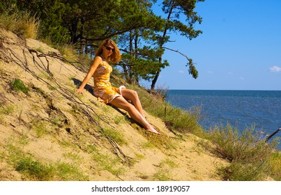 Young woman sitting on dune in the forest