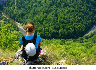 Young woman sitting on edge of cliff and admiring the wild virgin forests of Romania (Padurea Craiului) after exiting a via ferrata route (Casa Zmeului) on a sunny day of summer, helmet on backpack