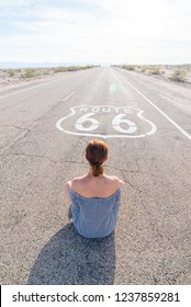 Young woman sitting on an endless straight empty road in the middle of nowhere on the Route 66 road. Backpackers, visionary, entrepreneur, adventure concepts.