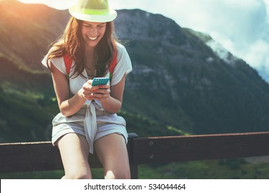 Young woman sitting on the fence with mobile phone. High mountains touristic path at sunset. Digital communication. Texting with friends in social network