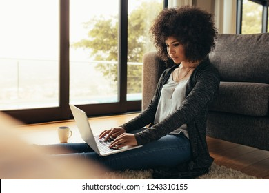 Young woman sitting on floor by the couch using laptop. African female working on laptop computer at home.