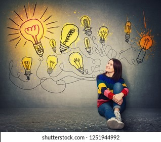 Young woman sitting on the floor smiling looking at bright lightbulbs on the wall. Smart and ingenious girl has a different thinking, genius creativity concept, alternative idea as the way to success.
