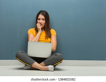 Young woman sitting on the floor with a laptop biting nails, nervous and very anxious
