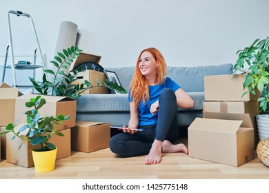 Young woman sitting on floor in new apartment with tablet and looking away